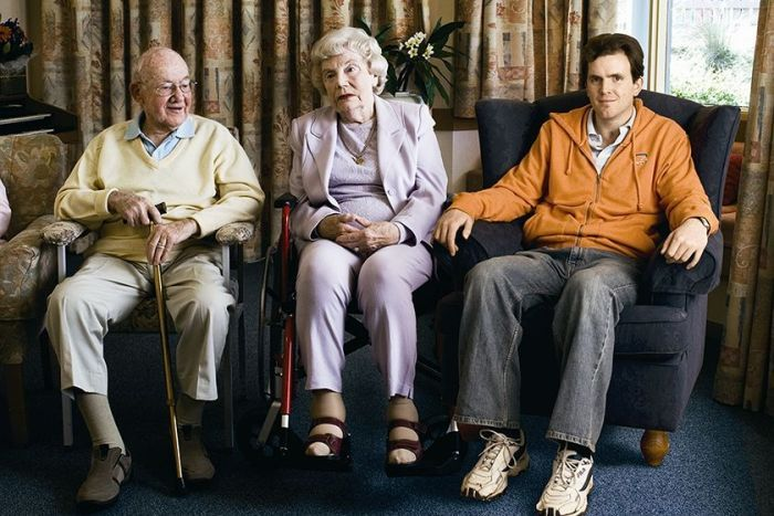 Grayden Moore became a resident in a nursing home at the age of 23. He is one of hundreds of people with disabilities under 50 forced to live in aged care. (Fred Kroh (The Summer Foundation). Shown sitting with two elderly aged care residents.