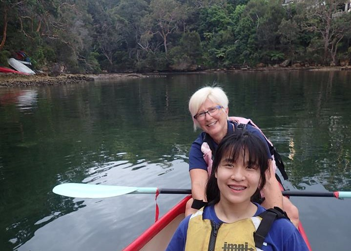 Nicole and friend on boating on a river. Nicole is smiling broadly.