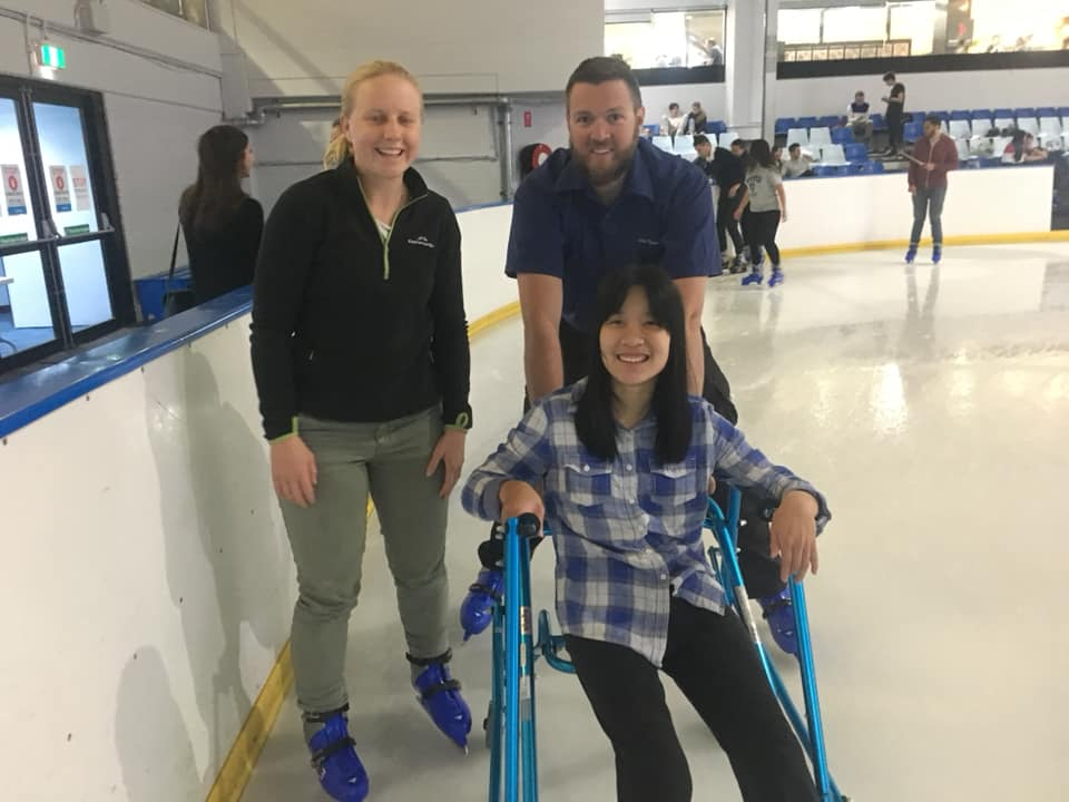 Nicole and two friends standing on an ice skating rink. Nicole is supported and in a semi-seated position by a mobility aid, all are smiling broadly.