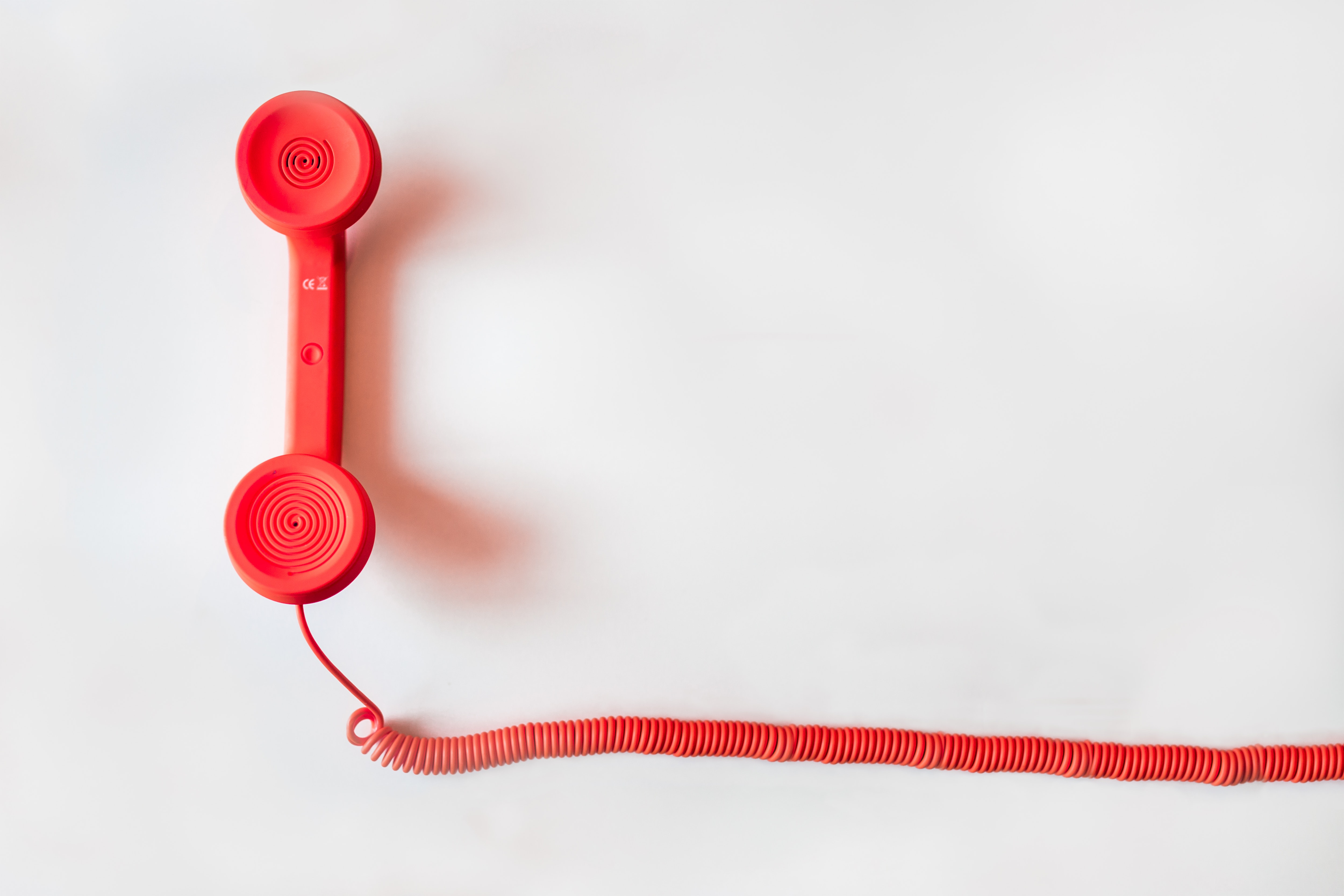 A red corded telephone handset