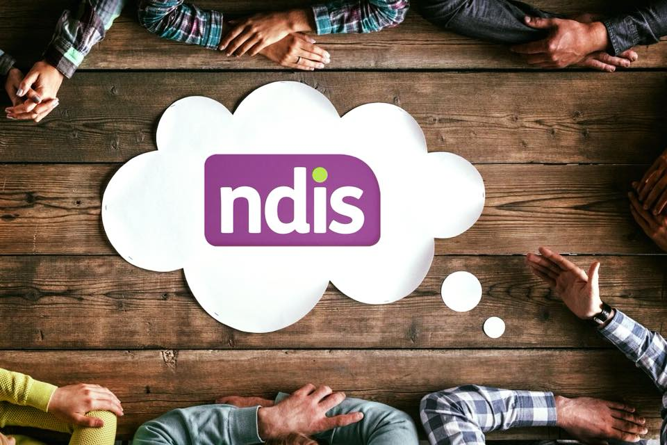 ndis logo in a white cloud on a wooden table top with people's arms folded around the outside