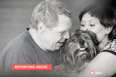 Man with a disability hugging a scruffy dog tha is being held by a woman