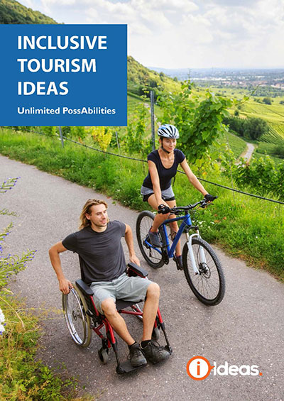 Inclusive Tourism IDEAS: Unlimited Possibilities. Book Front Cover. Image of man in wheelchair and woman on bike rolling down a roadway with a vibrant green valley in the background.