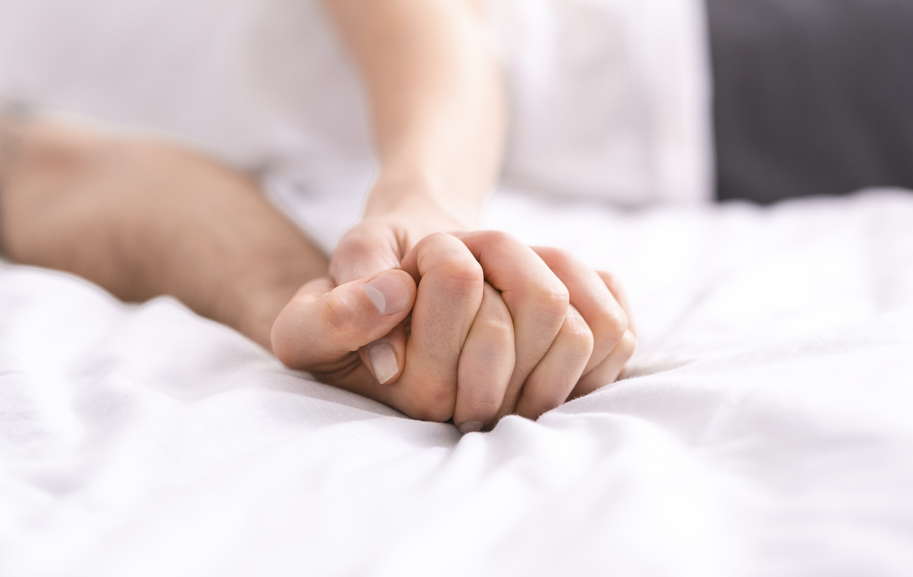 detail of couple's hands clasped tightly on a bed