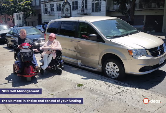 A couple infront of an accesible vehicle in San Fransisco, they are both seated, Carolyn in a wheelchair, Steve in an motorised scooter
