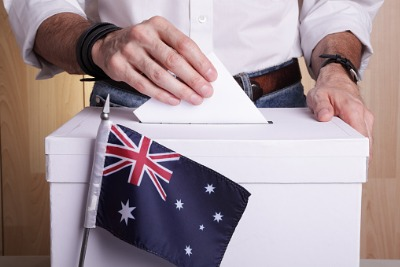 a man's hand above a ballot with a small Australian flag