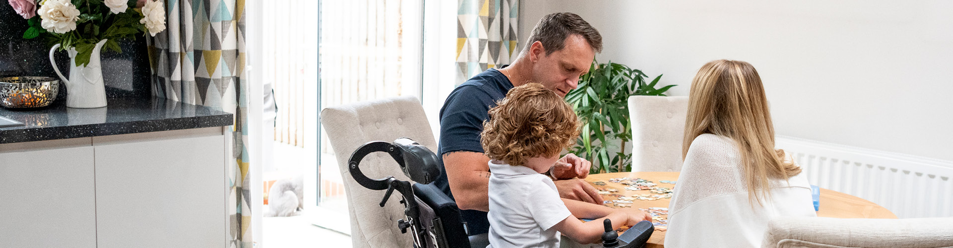 A father and two children doing a puzzle at a kitchen table. One child is a wheelchair user.