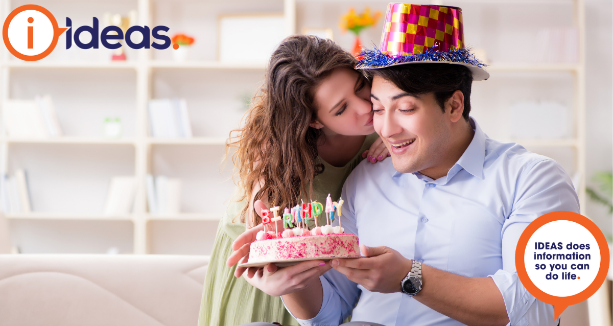 Young man celebrating his birthday with a loved one. He is holding a cake and wearing a party hat.