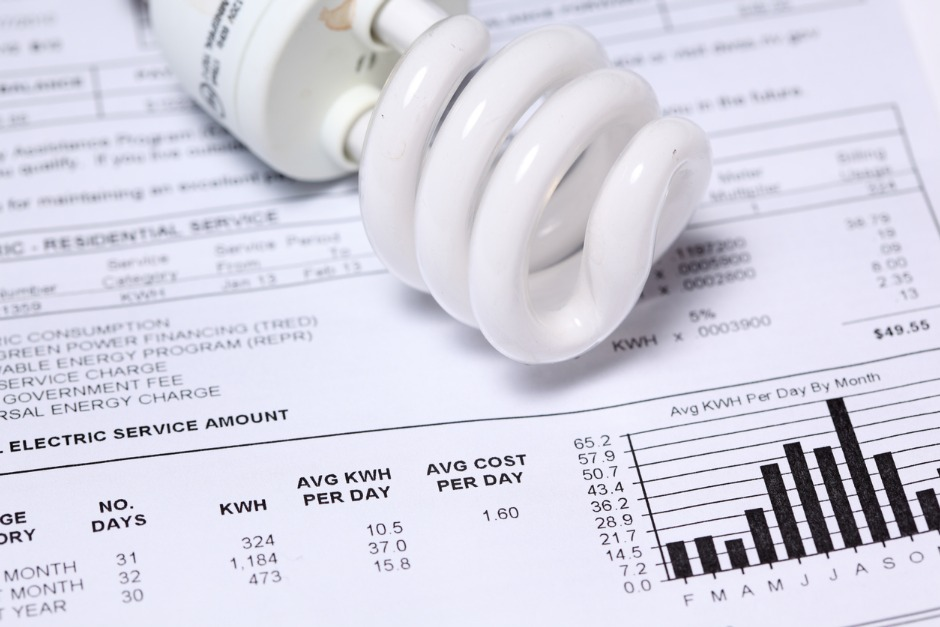 Electricity bill with bar graphs and an energy efficient light bulb
