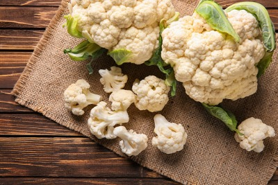 Fresh cauliflower and pieces on a hessian mat
