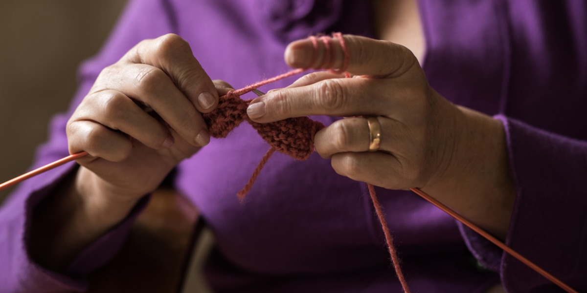 detail of older woman's hands knitting. she is wearing a purple jacket.