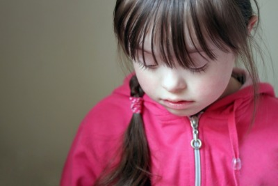 Image of young girl with Down Syndrome looking sad