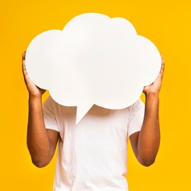Image of man holding empty speech bubble in front of his face.