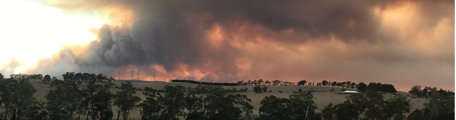 smoke from bushfire billows over tinder dry grassy hill