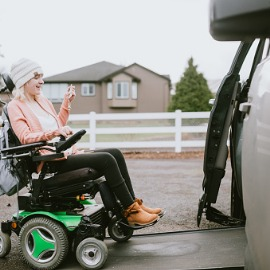 Image of young girl in wheelchair entering a wheelchair accessible vehicle.