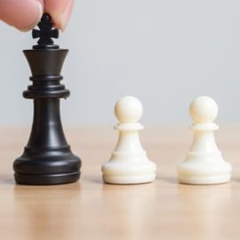 Image of of hand holding a black chess piece (King) with a row of white chess pieces (pawns).