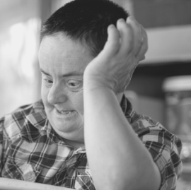 man with down syndrome leaning on his arm pensively
