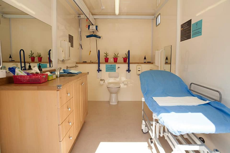 Image of interior of portable wheelchair accessible bathroom with toilet, hoist, adult sized change table and full vanity and separate basin.