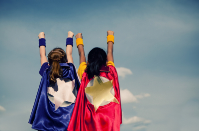 Two small girls with flowing superhero capes