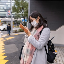 Image of woman on street wearing a medical mask