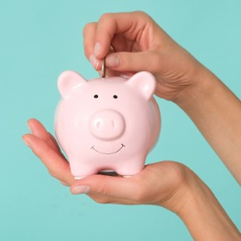 Image of hand placing a coin in a piggy bank