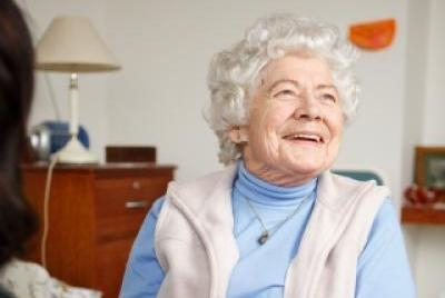 Elderly woman siting having her hands held