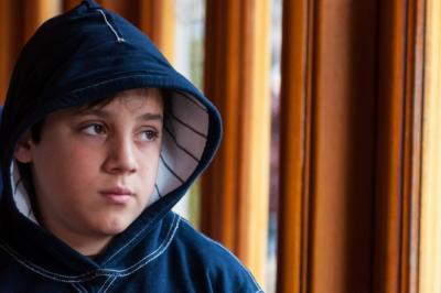Image of a young boy with a hoodie looking thoughtful