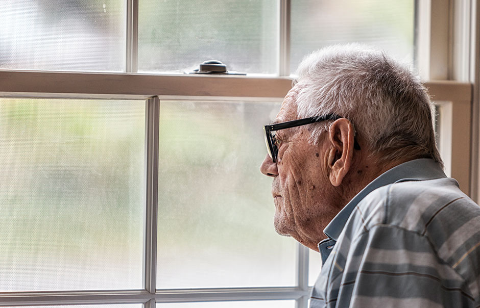 Elderly man looking through a window on a dark day
