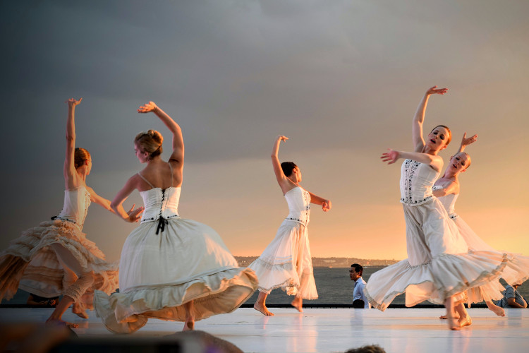 5 women in white dress dancing in a performance