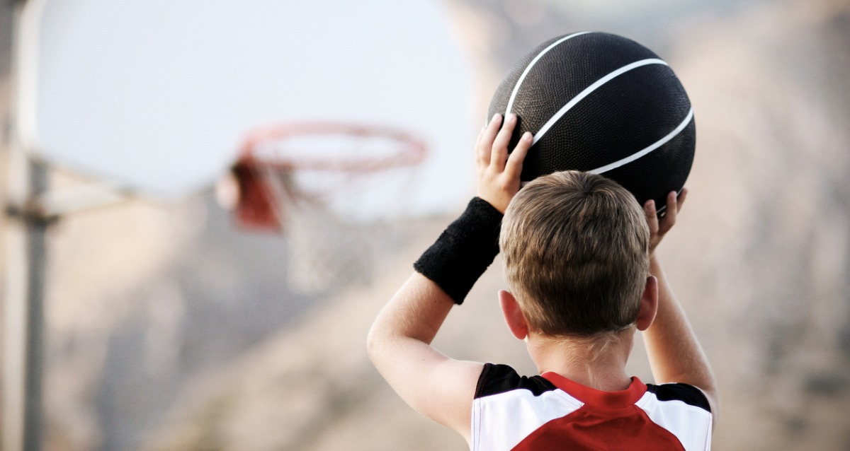 A young boy lining up a basketball shot