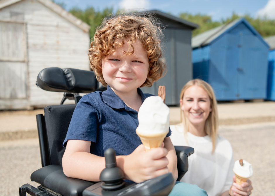Young boy in wheelchair holding an ice-cream. Beside him is a woman holding an ice-cream. In the background are beach huts.