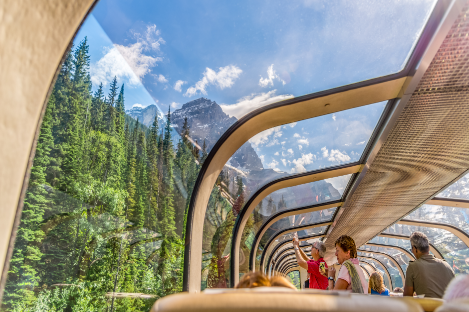 An image of the Canadian Rocky Mountains viewed from inside a train with a glass roof.
