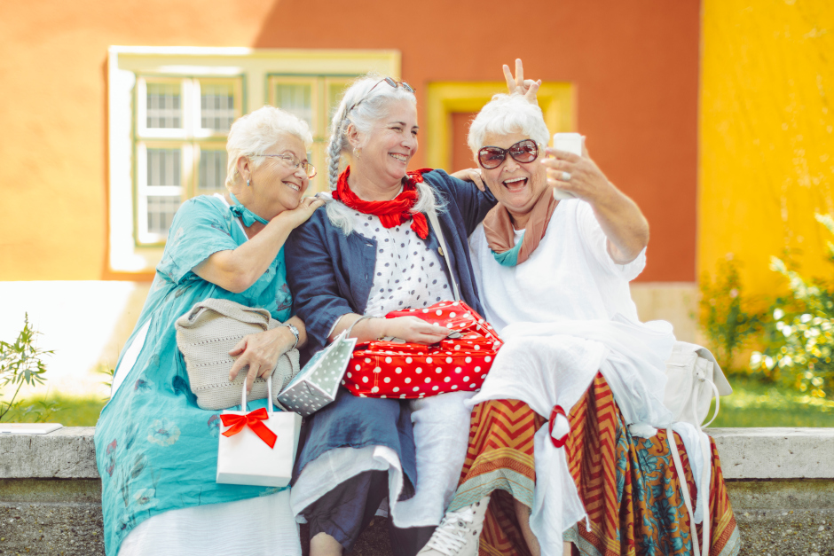 Image of three senior ladies. One is holding a phone adn they are all smiling for a selfie photo