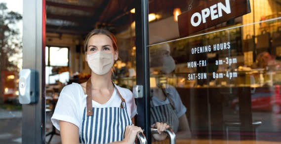 Waitress wearing a mask outside a cafe