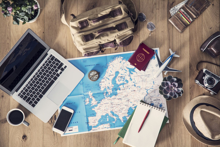 A travel concept flatlay with map, computer, passport, phone, notebook and camera