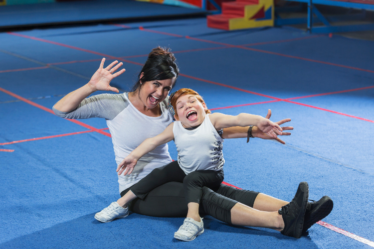 A young woman with disability and her Gymnastics instructor and playing up to the camera
