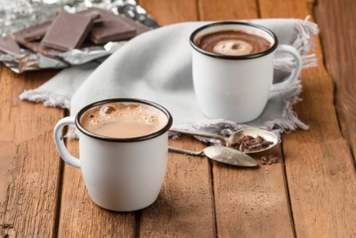 Two mugs of hot chocolate, two spoons and a napkin with pieces of chocolate in the background