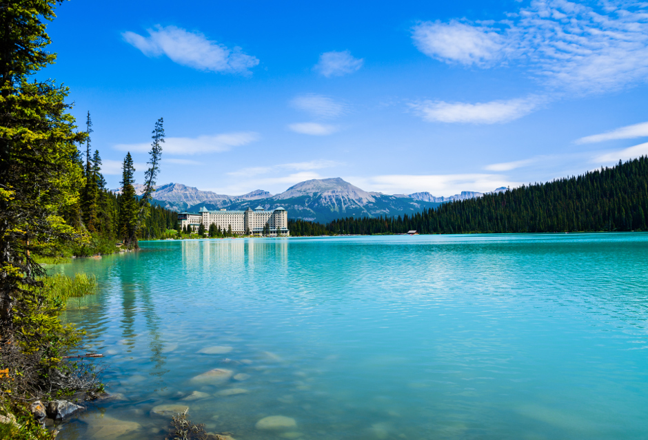 An image overlooking a blue lake with mountains in the background and Chateau Lake Louise