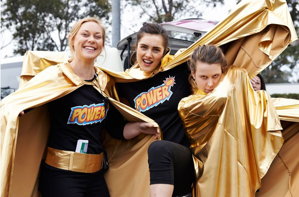 Three people with Power on there shirts and gold capes