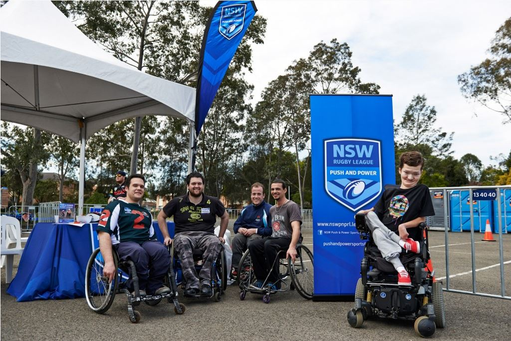 2x people in wheelchairs at a NSW Rugby League Stand