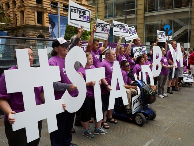 People in purple t-shirts holding giant white letters which spell #STANDBYME