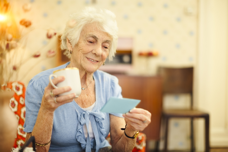 Image of a senior woman, holding a cup and blue letter.