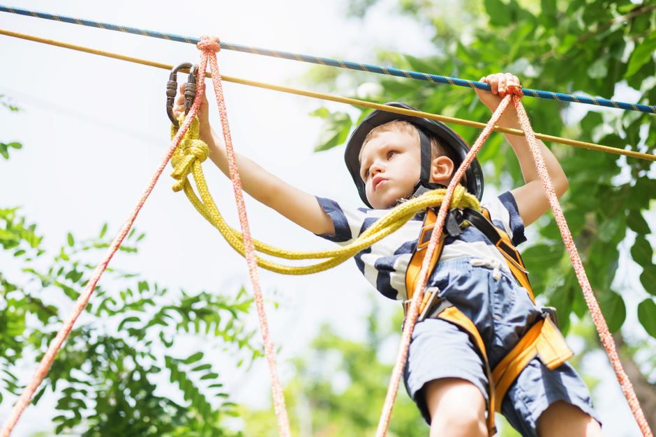 Image of small boy wearing helmet on rope course