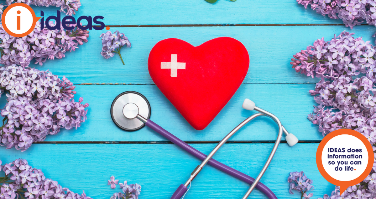 Red heart with bandaid in a cross shape, sit on a blue background. It is surrounded by lilac blooms, and a stethoscope.