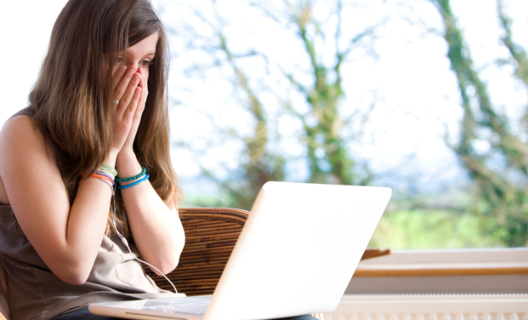 A girl with her hands covering her mouth in surprise or shock, She looks at a laptop.