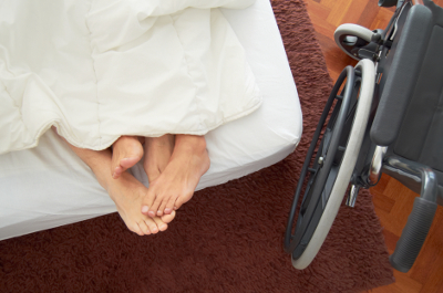 Image of a couple's feet sticking out from the covers in bed and a wheelchair parked alongside.