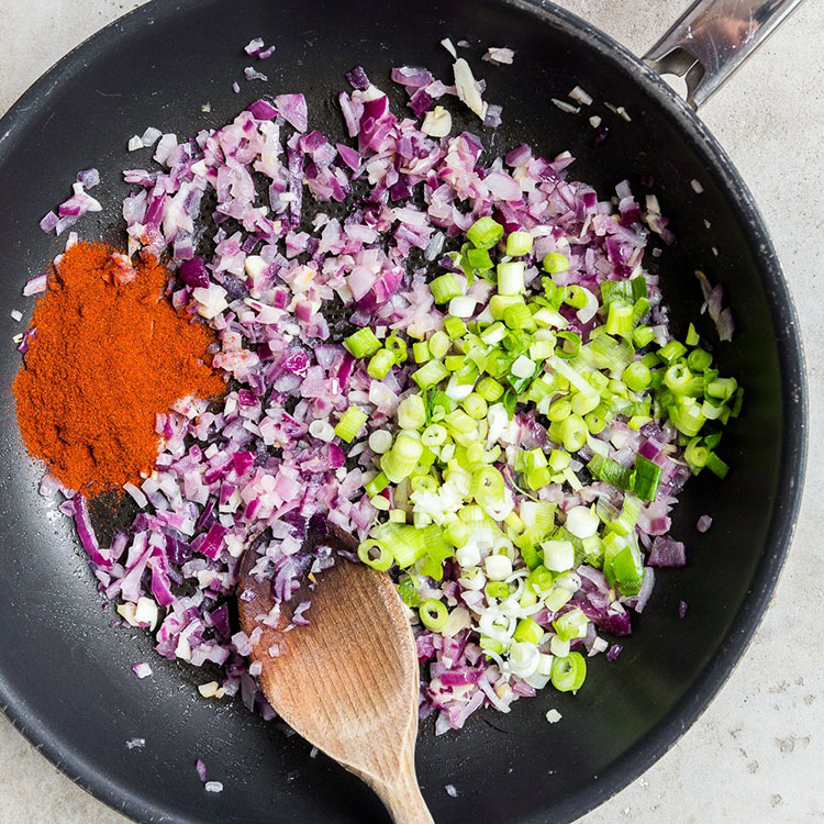 diced red onion, spring onions and paprika in a non-stick pan