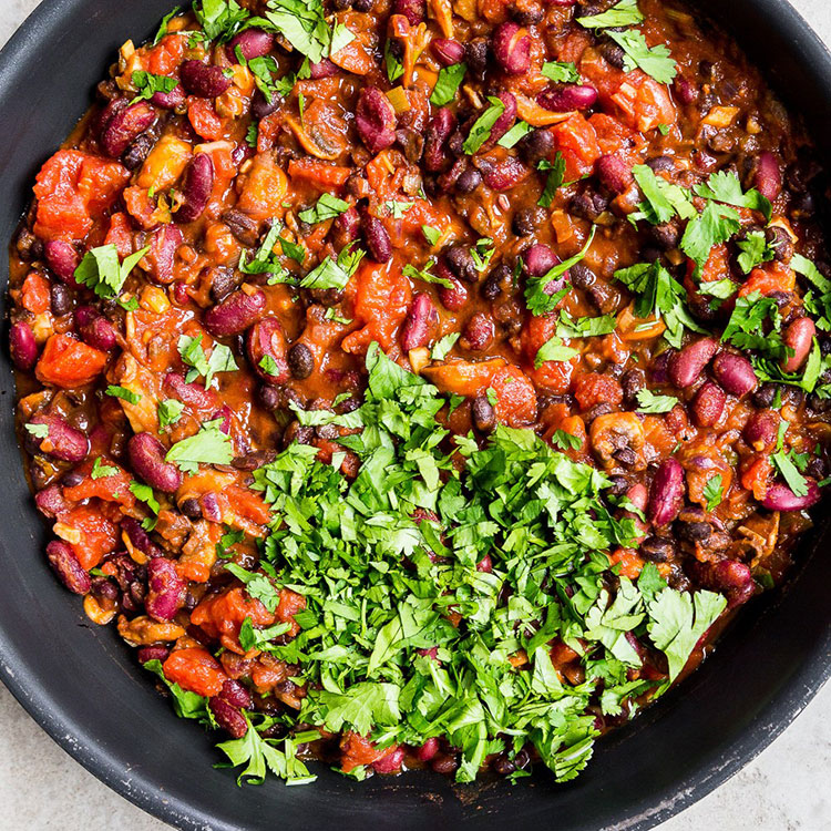 beans, onions, mushrooms, tomatoes with paprika and herbs in a non-stick pan