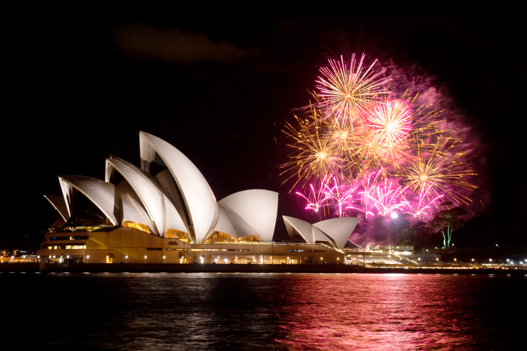 A photograph of the Sydney Opera House Sails overlooking the Harbour with fireworks in the night sky.