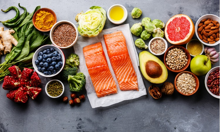 Image of healthy food, including vegetables, fruit and salmon, all laid out on a grey benchtop.